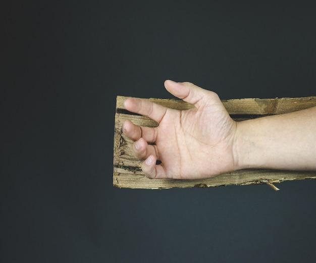 Hand van jezus christus op een houten kruis alvorens te worden genageld