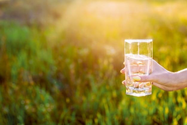 Hand van jong vrouwenwijfje met zuiver glas water openlucht in groen park bij zonnige warme lichte dag met lichte lekken. actieve outdoor lifestyle vrije tijd concept.