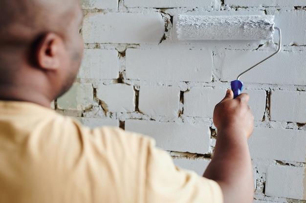 Hand van jonge afrikaanse man in beige t-shirt met verfroller terwijl hij voor bakstenen muur staat en het in witte kleur schildert