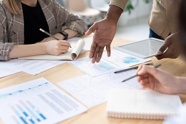 Hand van jonge afrikaanse zakenman wijzend op financieel papier op tafel tijdens het uitleggen van gegevens aan zijn collega's op werkvergadering in kantoor