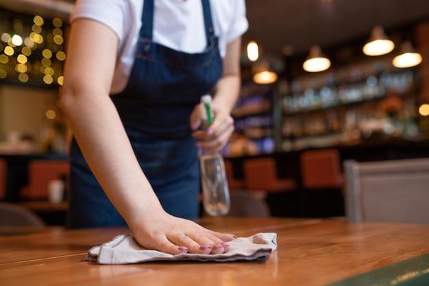 Hand van jonge eigentijdse serveerster die houten tafel met stofdoek en wasmiddel aan het eind van de werkdag afvegen