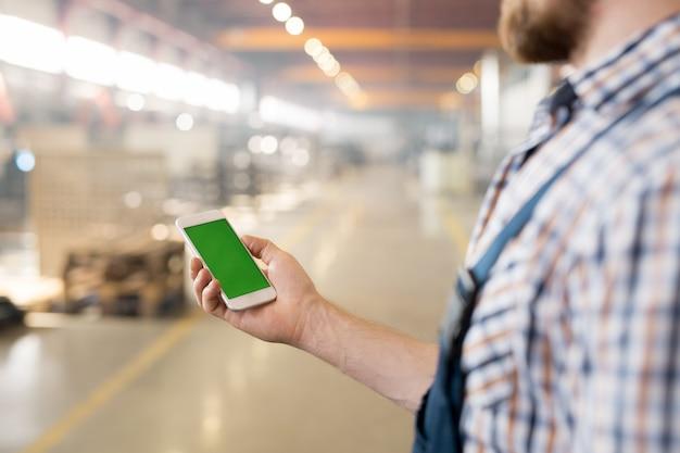 Hand van jonge fabrieksarbeider met touchscreen-gadget tijdens het gebruik tijdens pauze in de werkplaats