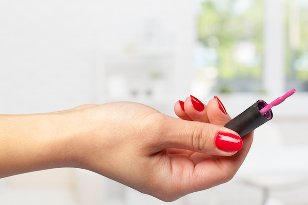 Hand van jonge het nagellakborstel van de meisjesholding