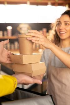 Hand van jonge serveerster in schort met twee kartonnen containers met eten en glas koffie over open zak terwijl ze doorgeven aan koerier