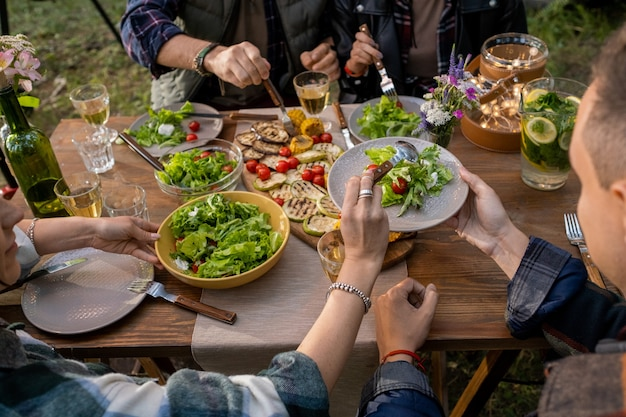 Hand van jonge vrouw die groentesalade op het bord van haar vriendje zet