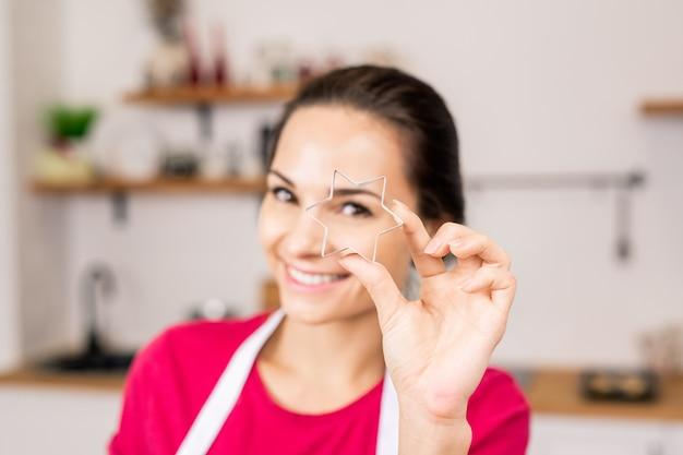 Hand van jonge vrouw met stervormige snijder voor zelfgemaakte koekjes terwijl deeg gaat snijden