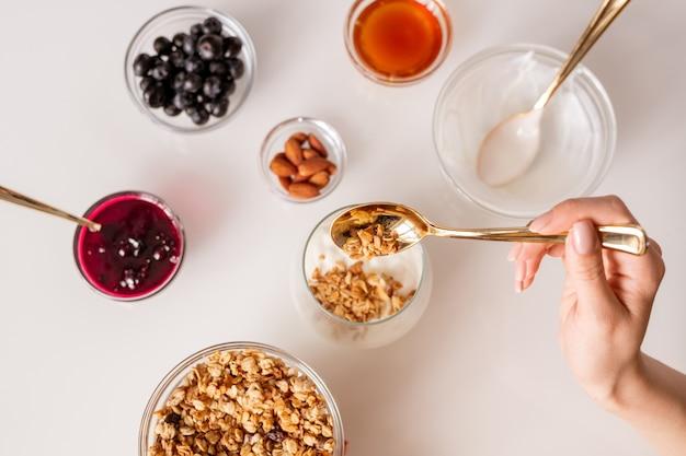 Hand van jonge vrouw met theelepel muesli aanbrengend glas met verse zure room tijdens het maken van yoghurt met jam, amandelnoten, honing en bessen