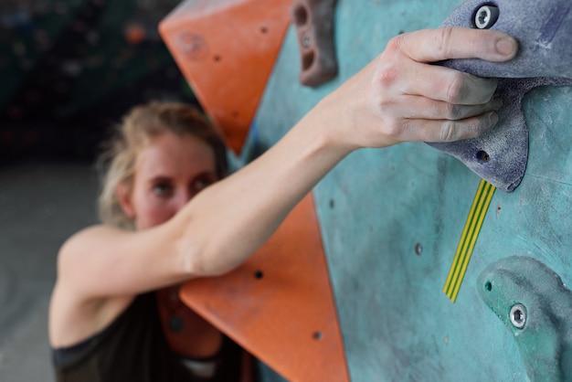 Hand van jonge vrouwelijke klimmer die zich vasthoudt aan een van de kleine kunstmatige rotsen terwijl hij probeert het bovenste punt van de klimmuur te bereiken