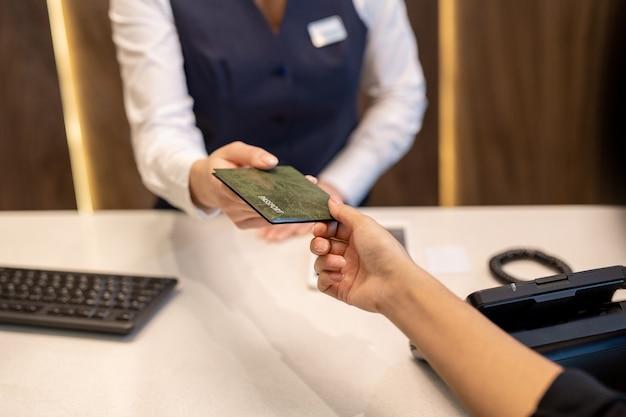Hand van jonge vrouwelijke receptioniste die paspoort doorgeeft aan een van de nieuwe hotelgasten bij de receptiebalie met telefoon en toetsenbord