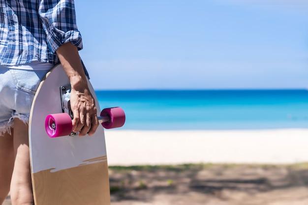 Hand van jonge vrouwen houden skateboard op het strand.