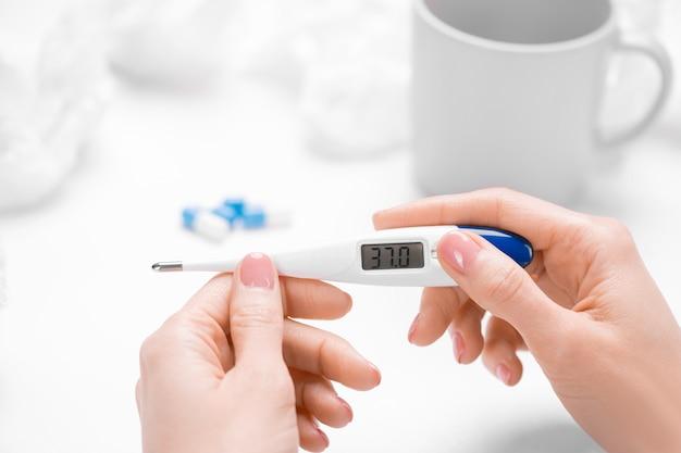 Hand van jonge zieke vrouwelijke bedrijfsthermometer met temperatuur van 37 graden boven tafel met mok, pillen en verfrommeld weefsel