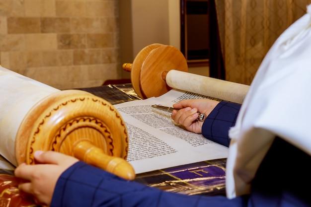 Hand van jongen die de joodse torah leest bij bar mitzvah bar mitswa torah lezing