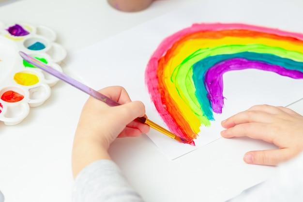 Hand van kind dat regenboog schildert tijdens de pandemie van het coronavirus.