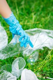 Hand van kind reinigt het park van plastic afval dat op het groene gras ligt