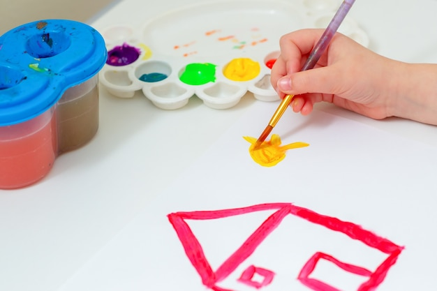 Hand van kind tekenen gele zon met rood huis met penseel en aquarellen op wit vel papier. kunstwerkconcept.