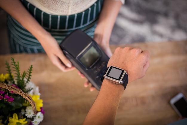 Hand van klant die betaling doet door smartwatch