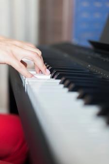 Hand van klassieke muziekartiest die piano of elektronische synthesizer speelt (pianotoetsenbord)