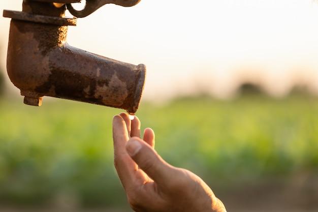 Hand van landbouwer die op water van uitstekende openluchtwaterpomp wacht. voor droogte seizoen concept