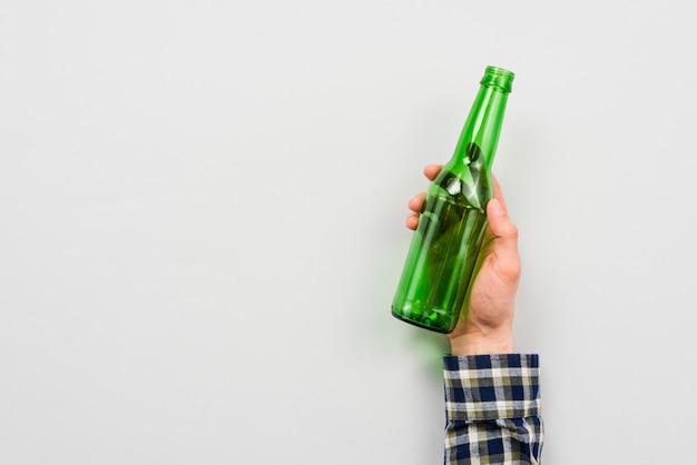 Hand van man met glazen fles