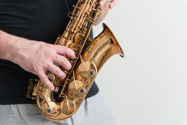 Hand van man spelen op saxofoon