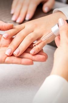 Hand van manicure giet olie door pipet op nagelriem van nagels van jonge vrouw in de schoonheidssalon. franse manicure