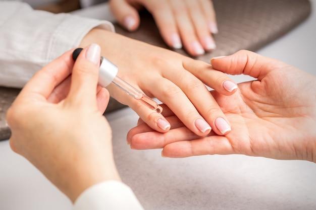 Hand van manicure giet olie door pipet op nagelriem van nagels van jonge vrouw in de schoonheidssalon