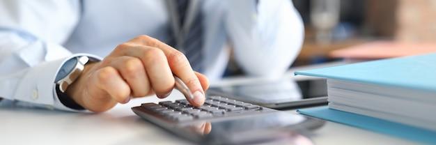 Hand van mannelijke businessperson berekeningen maken