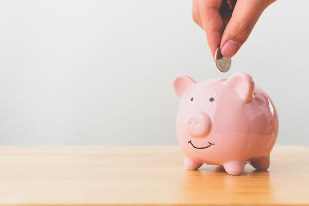Hand van mannelijke of vrouwelijke munten in piggy bank zetten