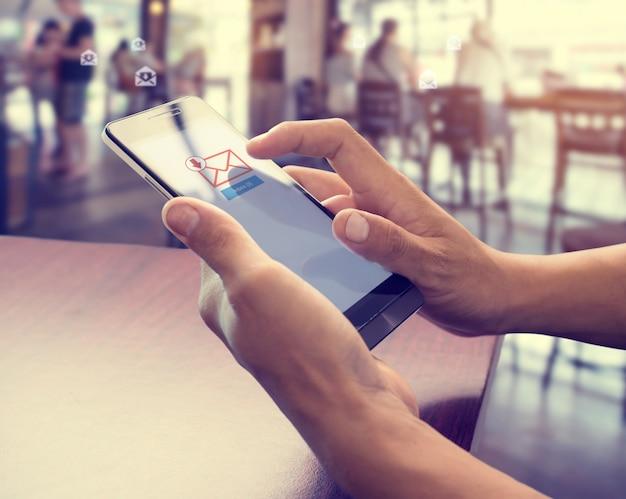 Hand van mannetje dat mobiele telefoon gebruikt om de post van het nieuwe e-mailbericht te openen