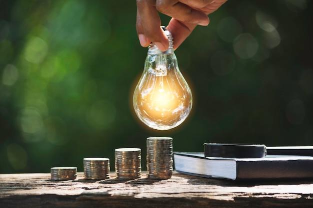Hand van mannetje die een gloeilamp met stapel van muntstukken en exemplaarruimte houden voor boekhouding, ideeën en creatief concept.