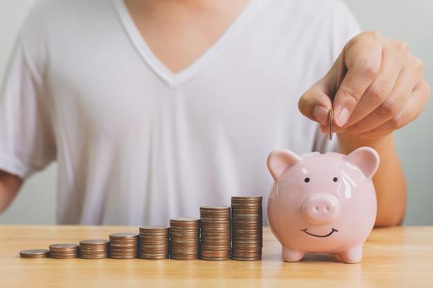 Hand van mannetje die muntstukken in spaarvarken met van de de stap groeiend groei van de geldstapel de besparingsgeld zetten