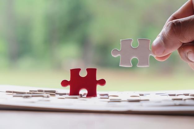 Hand van mannetje die puzzel zetten die op houten bureau en aardachtergrond verbinden.