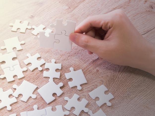 Hand van mannetje die puzzel zetten.