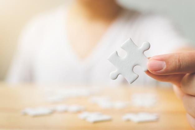 Hand van mannetje die stukken van witte puzzel op houten lijst proberen te verbinden