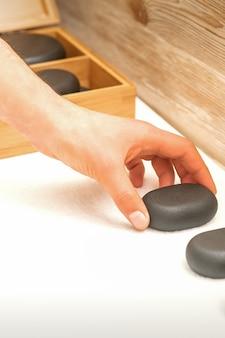 Hand van masseur legt massagestenen op tafel in spa salon