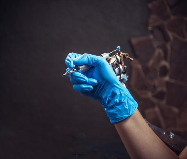 Hand van meester van de kunst van het tatoeëren en een tattoo-machine