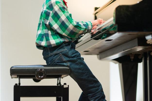Hand van meisje in mooie jurk piano spelen