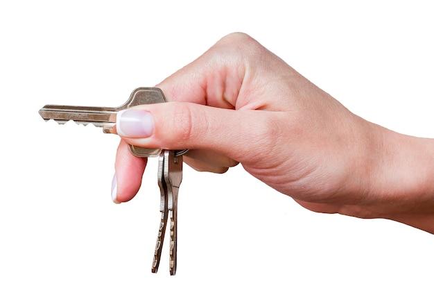 Hand van meisje met sleutels van huis of auto op wit