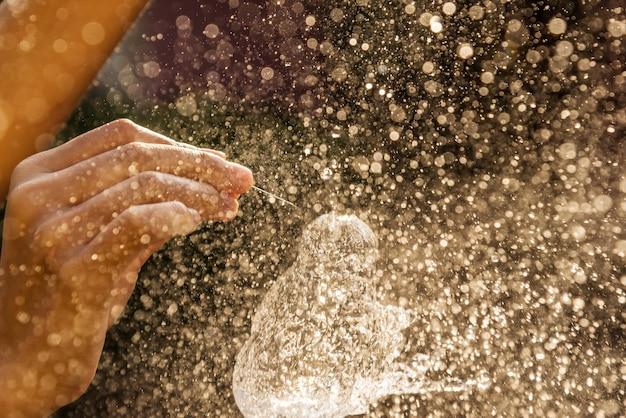 Hand van meisje met waterplons op zwarte achtergrond