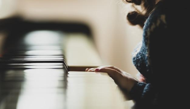 Hand van meisjepeuter die de piano speelt.