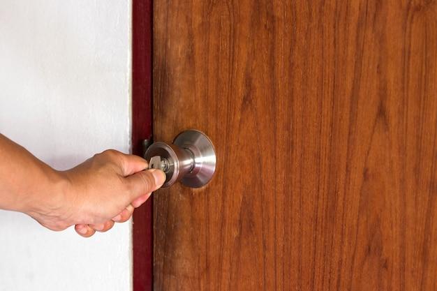 Hand van mensen opent de deur naar binnen