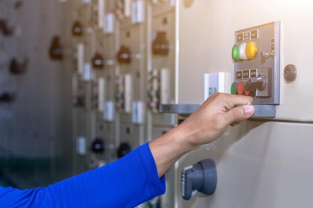 Hand van mensen sleutelschakelaar select-modus in het elektrische bedieningspaneel bevat schakelknoppen voor het bedienen van industriële machines en fabrieksapparatuur in de industrie
