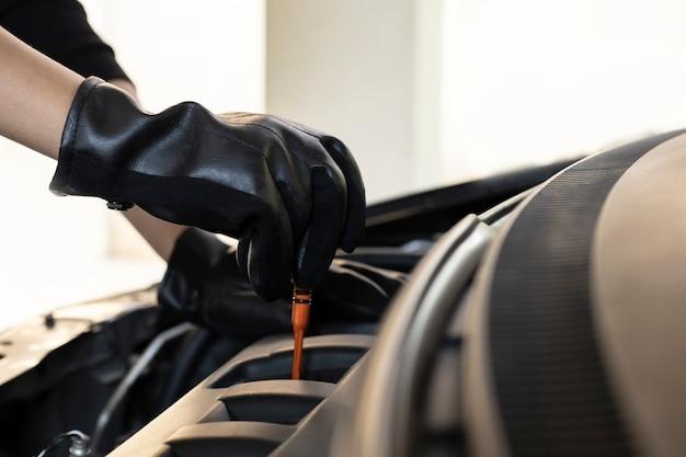 Hand van motorolie van de auto de mechanische controle voor onderhoud in de auto van de garagedienst.