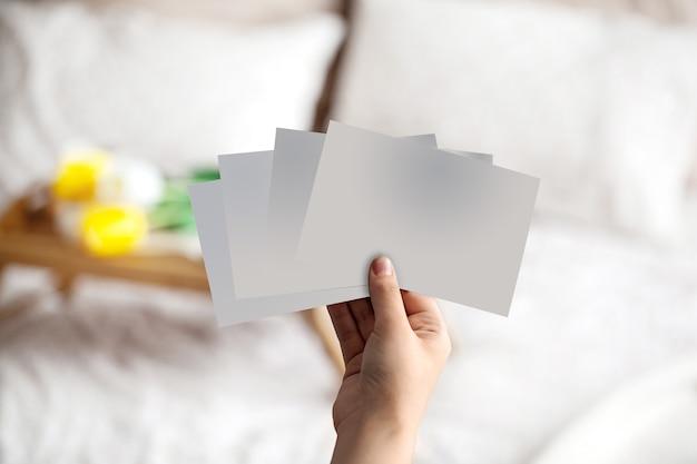 Hand van onbekende persoon die enkele lege stukjes papier vasthoudt