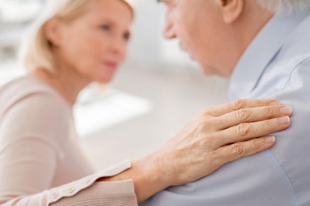 Hand van ondersteunende volwassen vrouw op schouder van rouwende man als een uiting van acceptatie en empathie