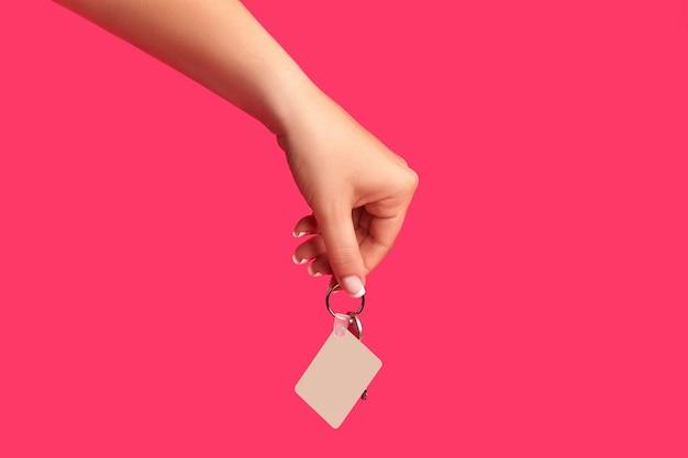 Hand van onherkenbaar vrouwtje houdt een sleutel met lege witte vierkante plastic sleutelhanger