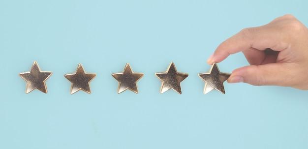 Hand van ontroerende stijging bij het verhogen van vijf sterren verhoog beoordelingsevaluatie en classificatieconcept