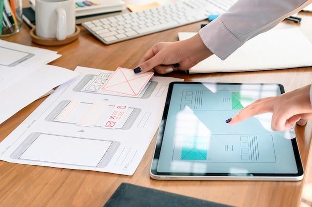 Hand van ontwerper creatieve grafische planning applicatie-ontwikkeling een prototype smartphone