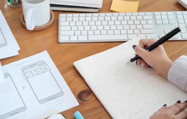 Hand van ontwerper creatieve grafische tekening applicatie-ontwikkeling een prototype smartphone
