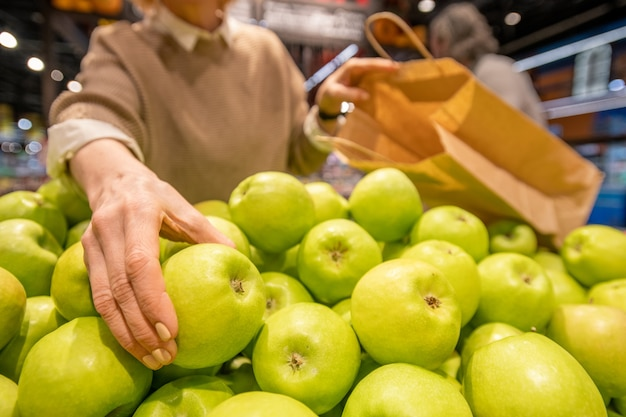 Hand van oude vrouw die met paperbag verse granny smith-appel neemt terwijl status door fruitvertoning in eigentijdse supermarkt